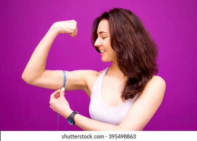 Fitness woman showing fresh energy flexing biceps muscles.