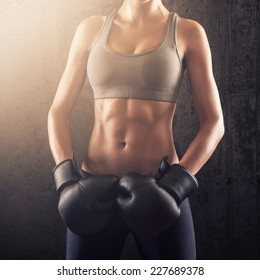 Fitness woman showing strong abs with boxing gloves on her hands