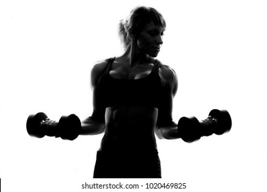 Fitness woman silhouette posing with dumbbells over white