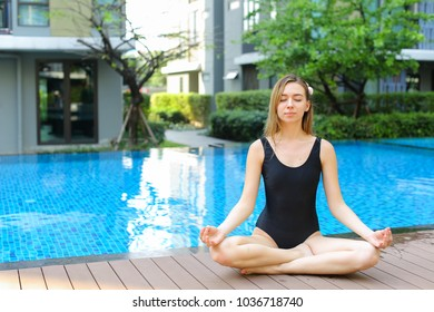 fitness woman sitting in lotus position doing yoga by swimming pool on sunny day. concept of physical or mental action, supreme being or receive good karma