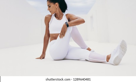 Fitness woman sitting on floor and twisting her back sideways. Woman in white fitness clothes holding one leg close and turning to her side to stretch her back.
