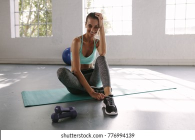 Fitness woman sitting on floor and relaxing after workout. Smiling female at gym taking a break from workout.