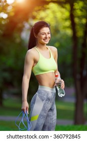 Fitness woman with a skipping rope and a bottle of water outdoors. Fitness classes outdoors. Attractive fitness woman. Workout outdoors. Healthy lifestyle