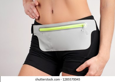 Fitness woman in sport shortwith waist bag for smartphone on white background