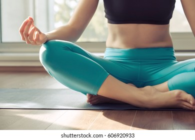 Fitness woman in sports clothing doing yoga at home in front of window at sunny day