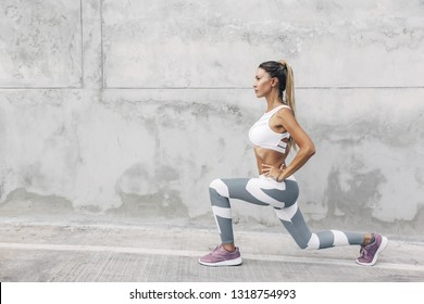 Fitness woman in sportswear doing squat exercise on the city street over gray concrete background. Outdoor sports clothing and shoes, urban style.