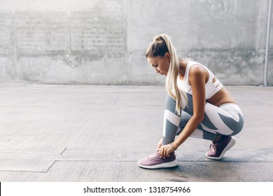 Fitness woman in sportswear tie on the city street over gray concrete background. Outdoor sports clothing and shoes, urban style.