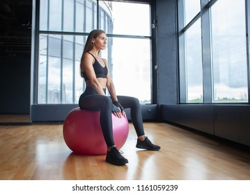 fitness woman in sportwear sitting on fit ball in gym