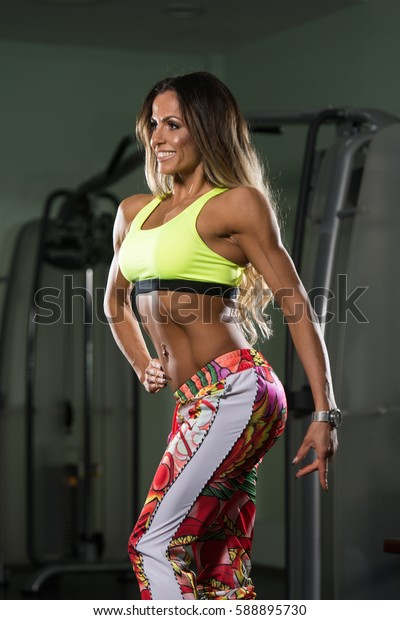 Fitness Woman Standing Strong In The Gym And Flexing Muscles - Muscular Athletic Bodybuilder Model Posing After Exercises