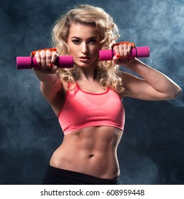 Fitness woman standing with weights