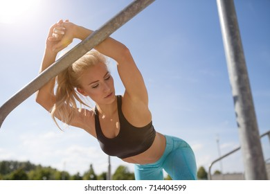 fitness woman stretching hot body in sunlight