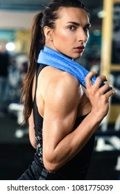 Fitness woman sweating. Beautiful sport girl with towel and sweat looking at camera tired, exhausted and sweaty after gym exercise. Multiracial female fitness model isolated on blurred background.
