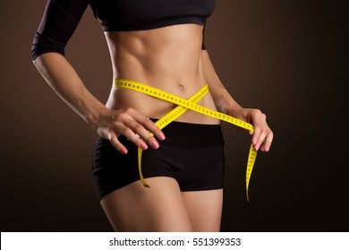 Fitness Woman With Tape Measure Showing Her Waist Isolated On Brown Background