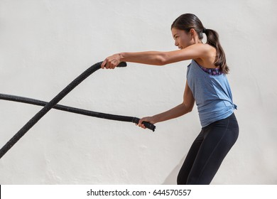 Fitness woman training battle ropes workout at gym. Girl working out arms and cardio using battling rope for cross fit exercises.