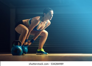 Fitness woman training by kettlebell.