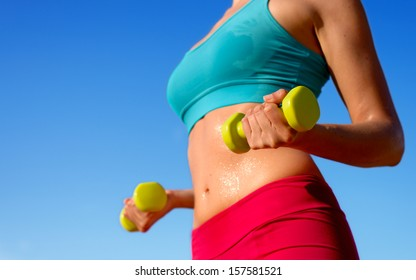 Fitness woman training hard with dumbbells and sweating in summer. Fit sporty girl exercising biceps and arms with weights on blue sky background.