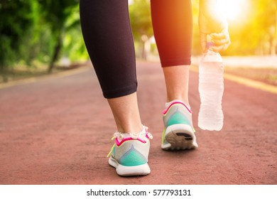 Fitness woman training and jogging in summer park, close up on running shoes and bottle of water in sunlight. Healthy lifestyle and sport concept