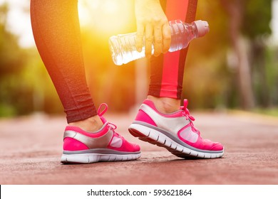 Fitness woman training and jogging in summer park, close up on running shoes and hand with drink water in sunlight. Healthy lifestyle and sport concept