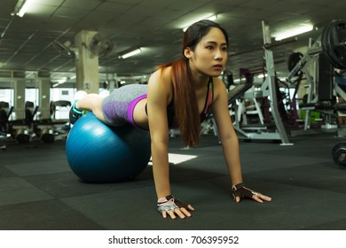Fitness woman in training showing exercises with pilates ball in gym, fitness concept, sport concept