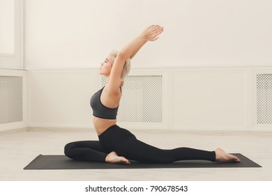Fitness, woman training yoga in camel pose in gym at white background, copy space. Young slim girl makes exercise, copy space