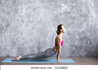 Fitness woman training yoga in cobra pose in gym. Yoga concept.