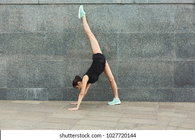 Fitness, woman training yoga in dog pose at gray wall background, copy space. Young slim girl makes stretching exercise.