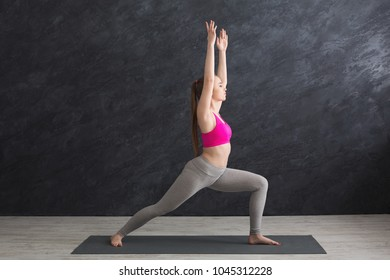 Fitness, woman training yoga in hero pose in gym at grey background, copy space, side view. Young slim girl makes exercise.