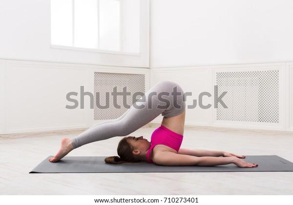 Fitness, Frauentraining Yoga in Pfluglage im Fitnessraum auf weißem Hintergrund, Kopienraum. Junge schlanke Mädchen trainiert.
