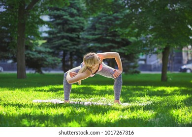 Fitness, woman training yoga pose outdoors in the park, copy space. Young slim girl makes exercise. Stretching, wellness, calmness, relax, healthy, active lifestyle concept