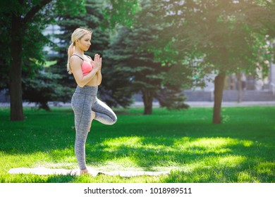 Fitness, woman training yoga in tree pose outdoors in the park, copy space. Young slim girl makes exercise. Stretching, wellness, calmness, relax, healthy, active lifestyle concept
