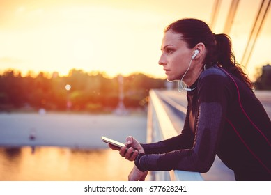 Fitness woman using smart phone and resting after running