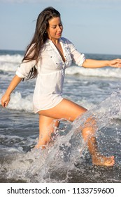 fitness woman walking along the shore of the beach getting wet with water