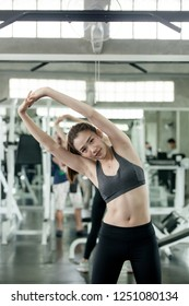 Fitness woman warming up in gym. Female doing warmup stretching workout on Gym background.