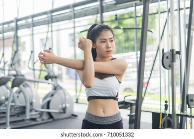 Fitness woman warming and stretching in gym, sport concept