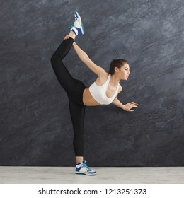 Fitness woman warmup stretching training at grey background indoors. Young slim girl making aerobics exercise, copy space