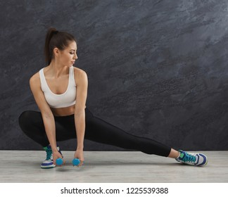 Fitness woman warmup stretching training at grey background indoors. Young slim girl making aerobics exercise, side view