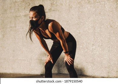 Fitness woman wearing protective face mask taking a break after a run. Female in sportswear resting after intense workout outdoors.