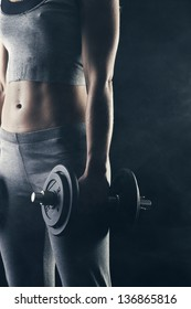 Fitness woman with weights on dark background