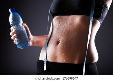 Fitness woman wet sporty belly after exercise with measuring tape and water bottle
