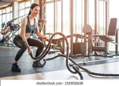 Fitness woman working out with battle rope at gym
