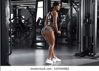 Fitness woman working out in gym. Active girl exercising. Sexy buttocks in thong