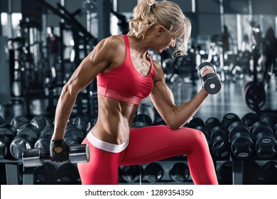 Fitness woman working out in gym, doing exercise for biceps. Muscular athletic girl