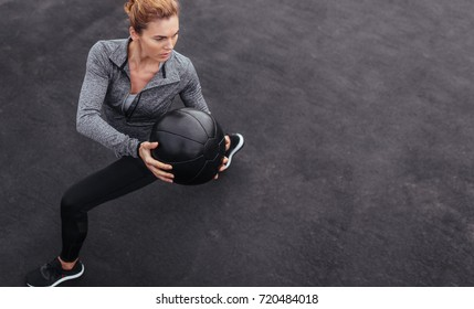 Fitness woman working out at outdoors gym using medicine ball. Sportswoman stretching outdoors with medicine ball. Copyspace for text.