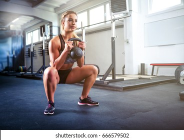 Fitness woman workout with kettlebell, training at cross fit gym