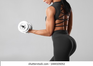 Fitness woman workout on gray background. Beautiful butt in leggings. Athletic girl with dumbbells