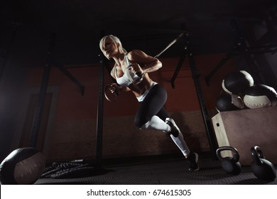 Fitness woman workout on the TRX in the gym. Fitness woman workout on the CrossFit. Fitness woman in the gym. Crossfit woman. Crossfit style. Training TRX straps. TRX gym
