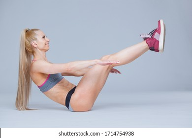 Fitness woman works her abs lifting her legs while lying on the floor isolated on grey background