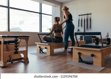Fitness women doing pilates workout sitting on a pilates machine in a gym. Rear view of a trainer guiding a woman doing pilates workout at the gym.