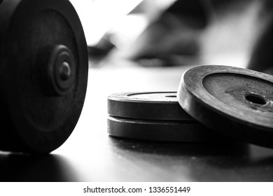 Fitness workout equipment. Dumbbell or barbell on a wooden floor surface. Black and white picture of success life style