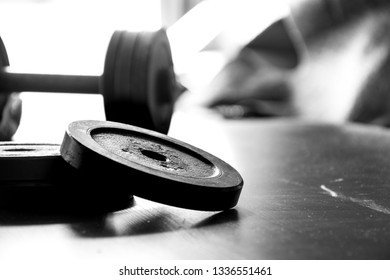 Fitness workout equipment. Dumbbell or barbell on a wooden floor surface. Black and white picture